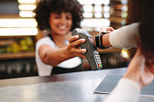 Customer making wireless or contactless payment using smartwatch. Store worker accepting payment over nfc technology.