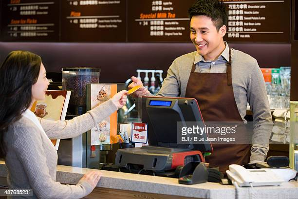 Customer paying by credit card in coffee shop