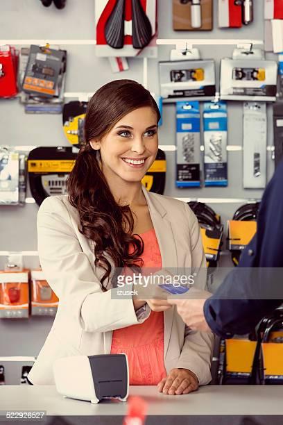 Cliente paga con tarjeta de crédito en la tienda de deporte