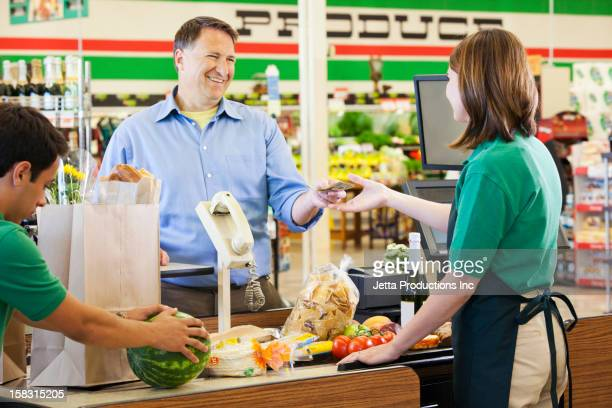 Customer paying cashier in grocery store