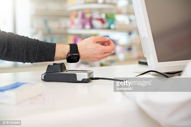 Customer paying cashless with smartwatch in a pharmacy