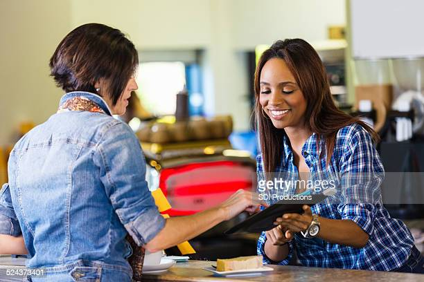 Customer paying for coffee with digital tablet credit card reader
