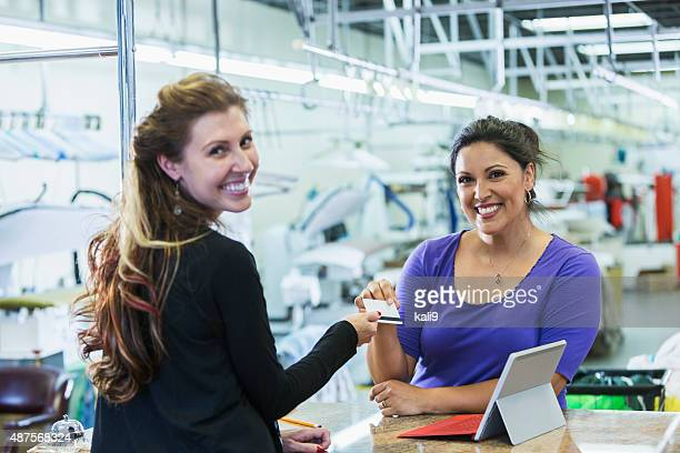 Customer paying for dry cleaning handing card to cashier
