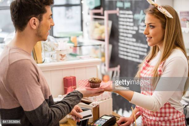 Customer paying muffin with credit card