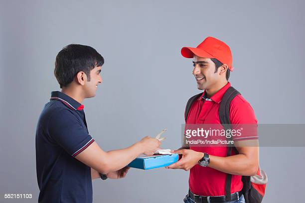 Customer paying pizza delivery man against gray background