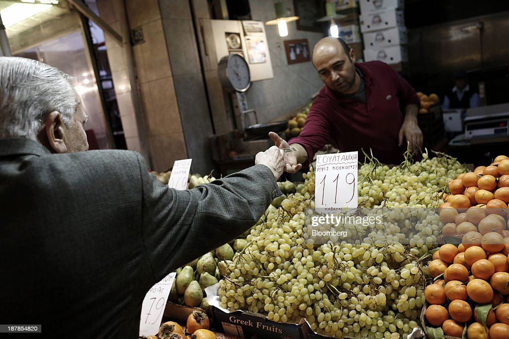 A customer pays a grocer for fresh fruit bought at his stall in the Kapani district market in Thessaloniki, Greece, on Wednesday, Nov. 13, 2013. Greece 'is following a fiscal adjustment program that aims to make the country's public finances sustainable on a permanent basis,' Finance Minister Yannis Stournaras told lawmakers during the debate, after holding talks with the troika earlier in the week. Photographer: Konstantinos Tsakalidis/Bloomberg via Getty Images