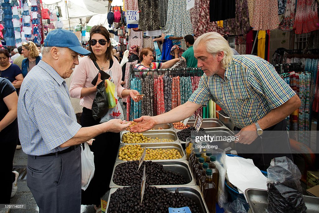 A customer pays a street trader for fresh olives at a market stall in Istanbul, Turkey, on Friday, June 7, 2013. The country's stocks and bonds have slumped this week as demonstrations spread nationwide after police used tear gas and water cannons on May 31 against demonstrators who had gathered in Gezi Park near Taksim to oppose plans to develop it. Photographer: Kerem Uzel/Bloomberg via Getty Images