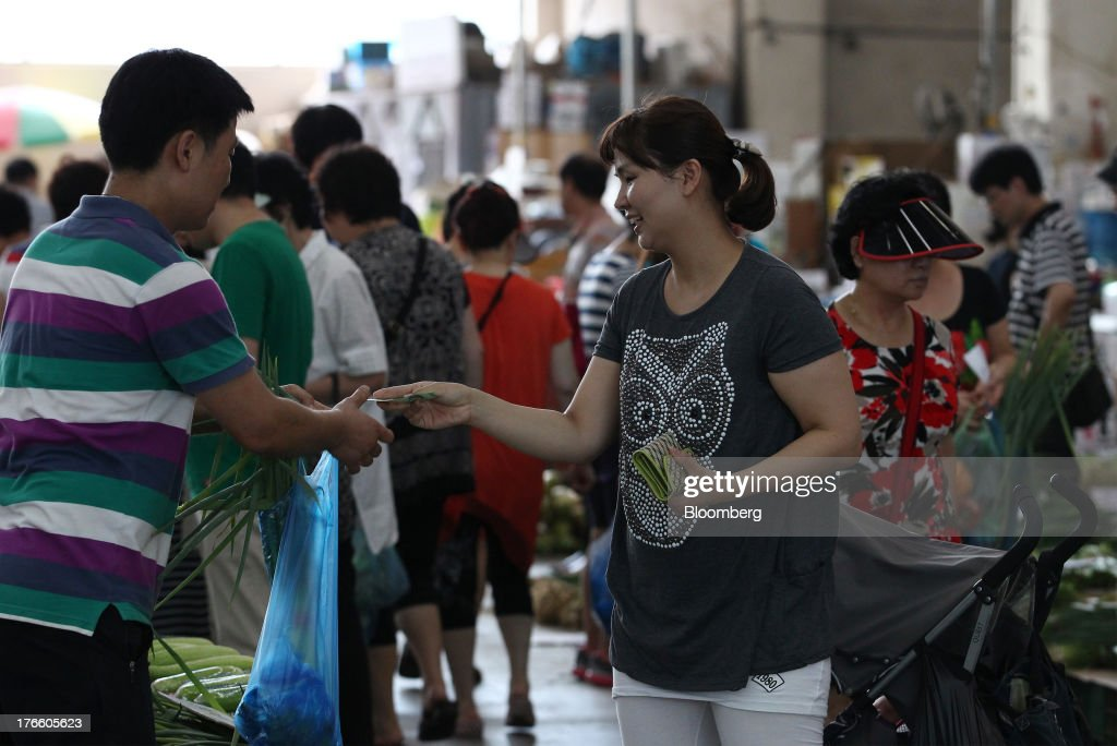 A customer pays a vendor for her purchases at Samsan Agricultural Wholesale Market in Incheon, South Korea, on Friday, Aug. 16, 2013. South Korean producer prices declined 0.9 percent in July from a year earlier after a 1.4 percent drop in June, the central bank said in a statement today. Photographer: SeongJoon Cho/Bloomberg via Getty Images