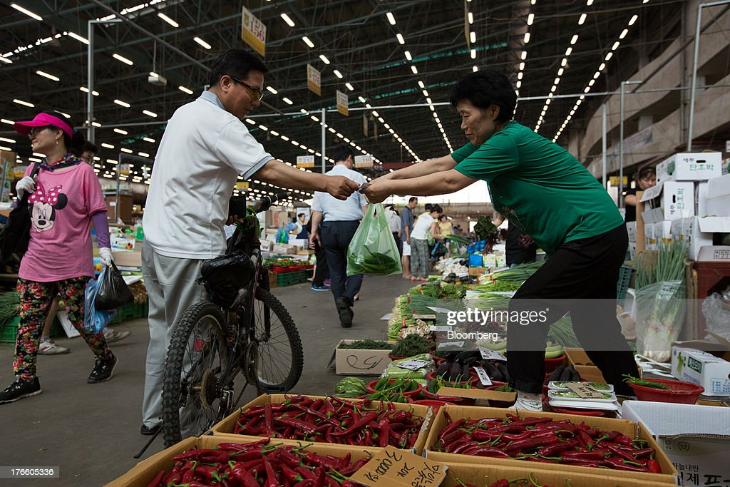 A customer pays a vendor for his purchase at Samsan Agricultural Wholesale Market in Incheon, South Korea, on Friday, Aug. 16, 2013. South Korean producer prices declined 0.9 percent in July from a year earlier after a 1.4 percent drop in June, the central bank said in a statement today. Photographer: SeongJoon Cho/Bloomberg via Getty Images