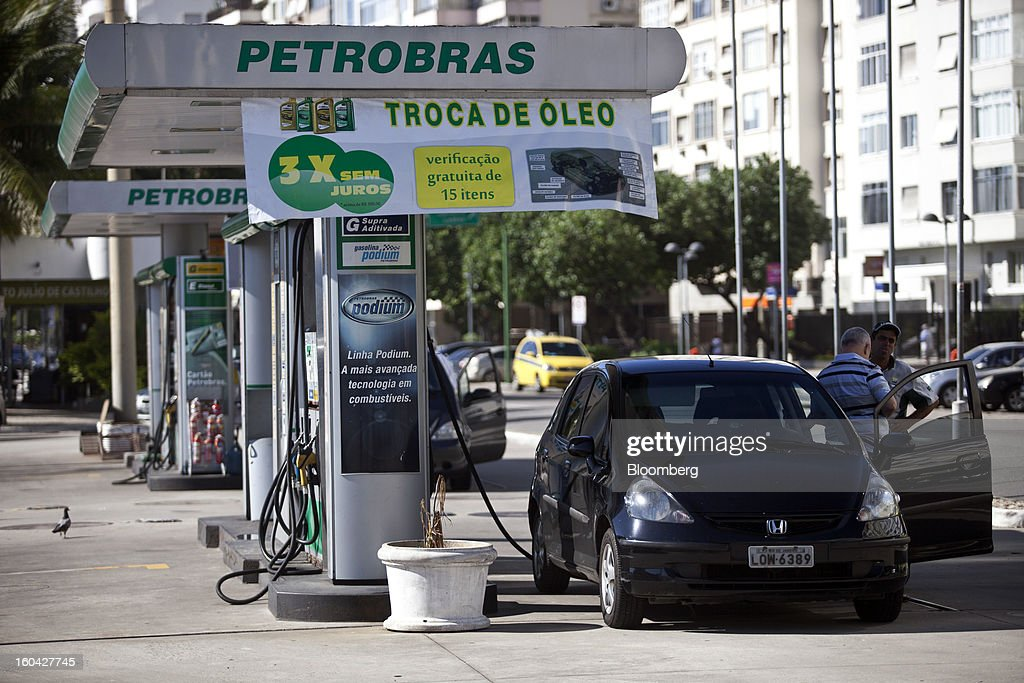 A customer pays an attendant at a Petroleo Brasileiro SA (Petrobras) station in Rio de Janeiro, Brazil, on Thursday, Jan. 31, 2013. State-controlled oil company Petrobras announced earlier this week that it would raise gasoline and diesel prices by 6.6 percent and 5.4 percent, respectively. Photographer: Dado Galdieri/Bloomberg via Getty Images
