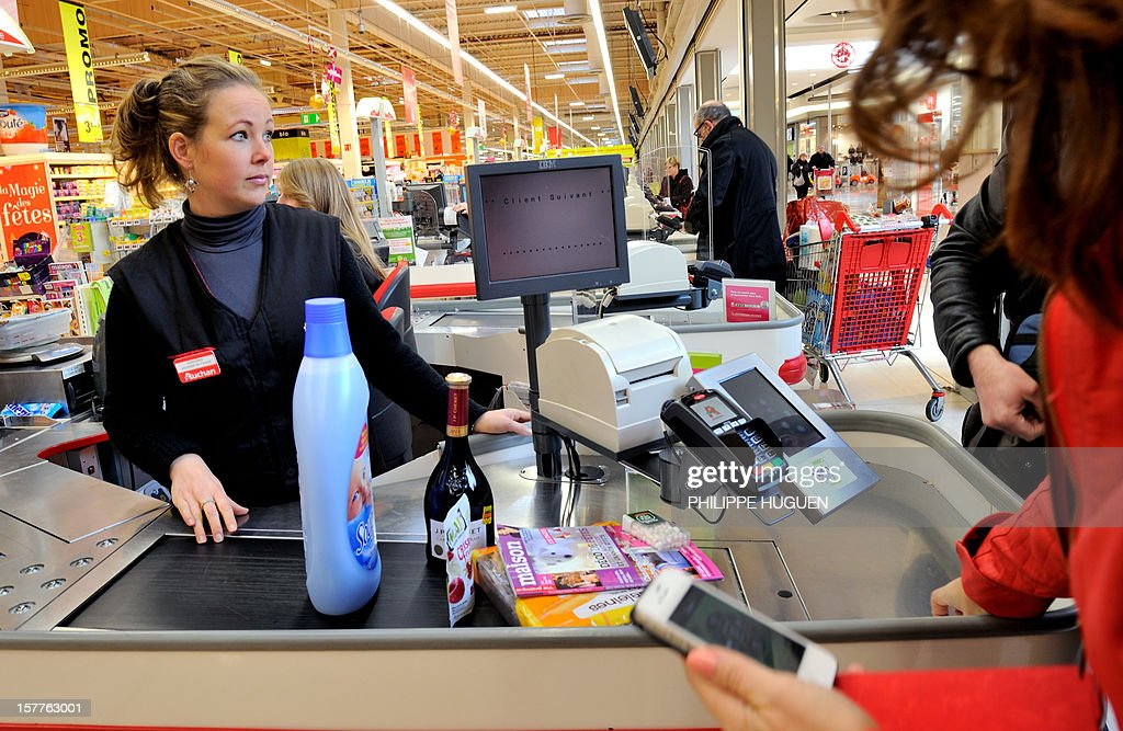 A customer pays at a register with a smartphone application on December 6, 2012 in a Auchan supermarket in Faches-Thumesnil near Lille, northern France. The 'flash and pay', an application developped by the Auchan group, allows customers to manage their shopping list, coupons, loyalty programs, budget and payments with their smartphones in any store offering the service. AFP PHOTO PHILIPPE HUGUEN