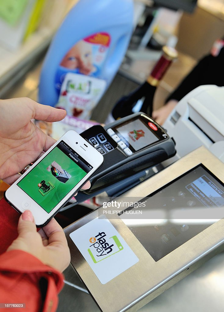 A customer pays at a register with a smartphone application on December 6, 2012 in a Auchan supermarket in Faches-Thumesnil near Lille, northern France. The 'flash and pay', an application developped by the Auchan group, allows customers to manage their shopping list, coupons, loyalty programs, budget and payments with their smartphones in any store offering the service.