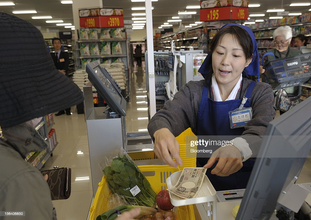 A customer pays at the check out counter in a Seiyu GK supermarket in Tokyo, Japan, on Wednesday, Nov. 14, 2012. Seiyu GK is a unit of Wal-Mart Stores Inc. Photographer: Akio Kon/Bloomberg via Getty Images