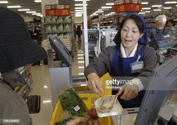 A customer pays at the check out counter in a Seiyu GK supermarket in Tokyo Japan on Wednesday Nov 14 2012 Seiyu GK is a unit of WalMart Stores Inc...
