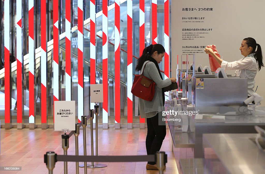 A customer pays for a purchase at the cashier counter at Fast Retailing Co.'s Uniqlo store in the Ginza district of Tokyo, Japan, on Wednesday, April 10, 2013. Fast Retailing, Asia's largest apparel retailer, is scheduled to announce earnings tomorrow. Photographer: Yuriko Nakao/Bloomberg via Getty Images