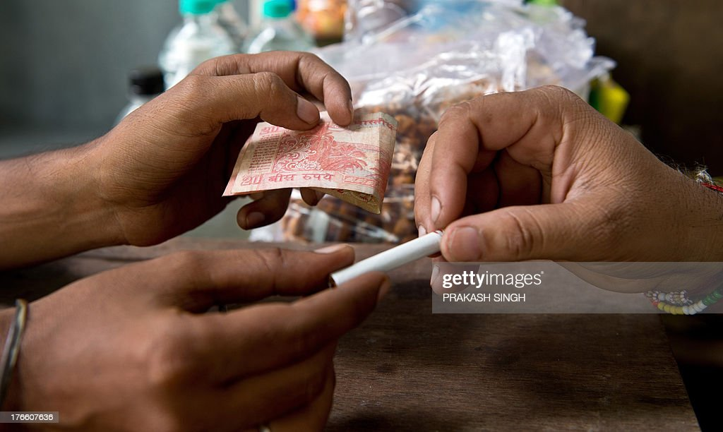 A customer pays for a single cigarette at a roadside stall in New Delhi on August 14, 2013. India's rupee plunged to a new record low against the dollar on August 16, and stocks slid 2.66 percent over fears that foreign capital could flow back to the United States as the US economy improves. The rupee, one of Asia's worst-performing currencies this year, hit a new low of 62.00 rupees to the greenback, slipping past its previous low of 61.80 rupees on August 6. AFP PHOTO/ Prakash SINGH
