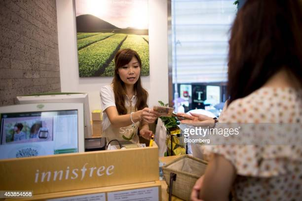 A customer pays for beauty products at Amorepacific Corp's Innisfree store in the Causeway Bay district of Hong Kong China on Wednesday Aug 20 2014...