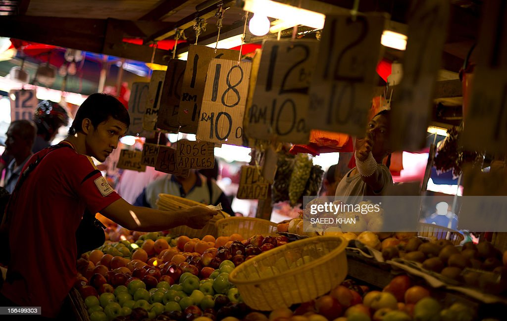 A customer pays for fruit at a vegetable market in down town Kuala Lumpur on November 16, 2012. The State bank of Malaysia announced that the economy expanded by 5.2 percent in the third quarter. AFP PHOTO / Saeed KHAN