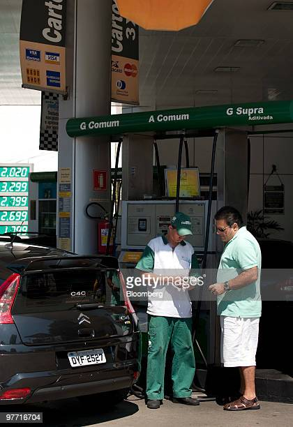 A customer pays for gas at a Petroleo Brasileiro SA gas station in Sao Paulo Brazil on Saturday March 13 2010 Petrobras may raise as much as $40...
