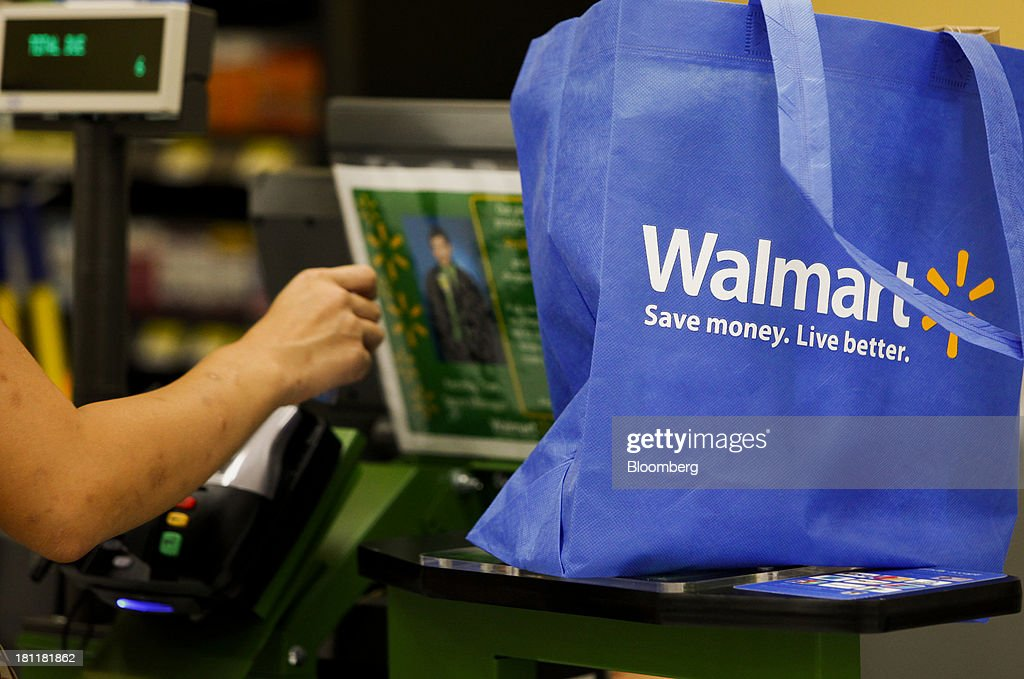 A customer pays for groceries during the grand opening of a Wal-Mart Stores Inc. location in the Chinatown neighborhood of Los Angeles, California, U.S., on Thursday, Sept. 19, 2013. Wal-Mart Stores Inc. will phase out 10 chemicals it sells in favor of safer alternatives and disclose the chemicals contained in four product categories, the company announced Sept. 12. Photographer: Patrick T. Fallon/Bloomberg via Getty Images