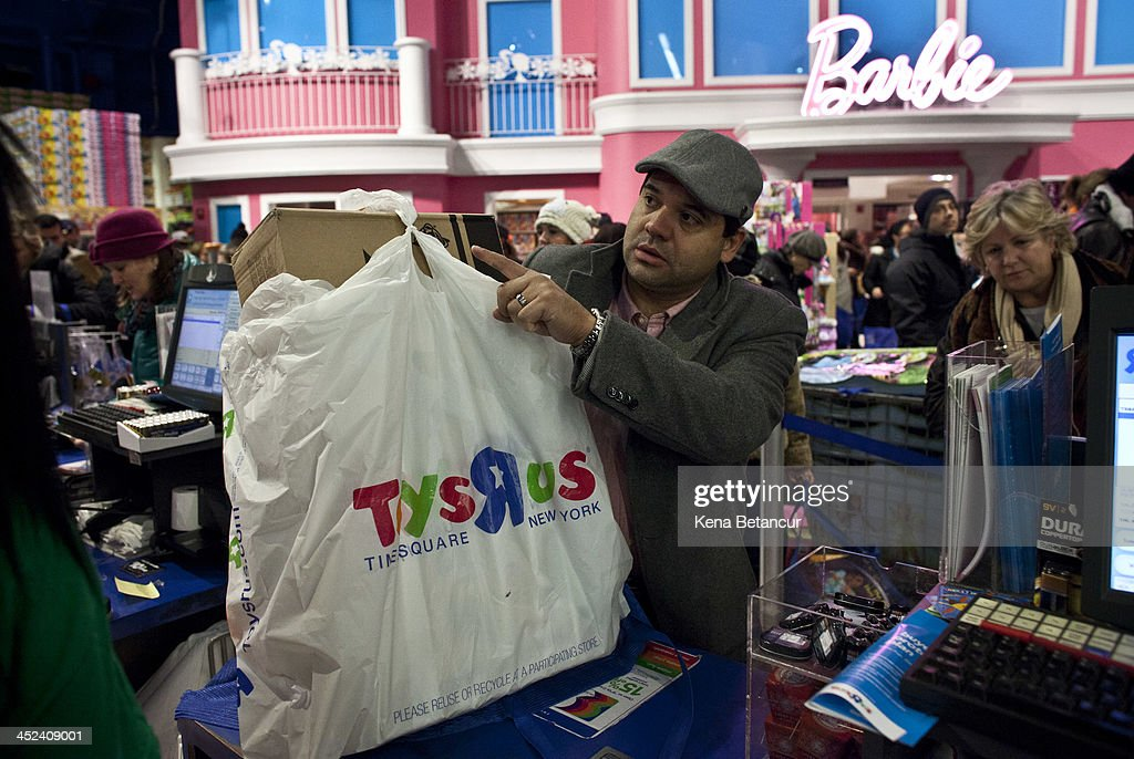 A customer pays for his items at Toys'R'Us in Times Square on Thanksgiving day on November 28, 2013 in New York City. Black Friday shopping began early again this year with most major retailers opening their doors on Thanksgiving day.