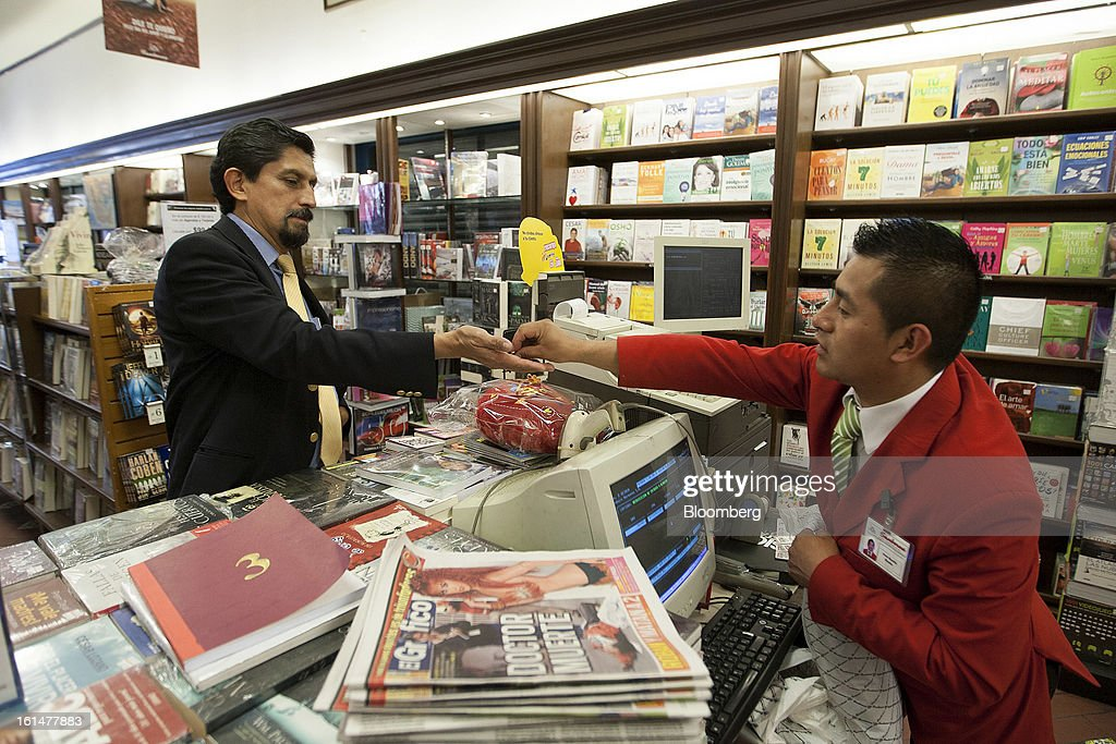 A customer pays for his purchases in the magazine and book section inside a Grupo Sanborns SAB store in Mexico City, Mexico, on Friday, Feb. 8, 2013. Grupo Sanborns SAB, the retailer controlled by Mexican billionaire Carlos Slim, raised 10.5 billion pesos ($825 million) in an initial public offering (IPO) last week and the total could climb to 12.1 billion pesos including an overallotment option for underwriters. Photographer: Susana Gonzalez/Bloomberg via Getty Images