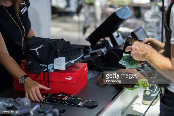 A customer pays for their purchases with euro banknotes inside a Puma SE sportswear clothing store in Berlin Germany on Tuesday July 25 2017 Puma...