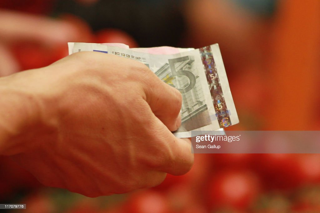 A customer pays for vegetables with Euro banknotes at a fruit and vegetable stand on June 21, 2011 in Berlin, Germany. Eurozone finance ministers are currently seeking to find a solution to Greece's pressing debt problems, including the prospect of the country's inability to meet its financial obligations unless it gets a fresh, multi-billion Euro loan by July 1. Greece's increasing tilt towards bankruptcy is rattling worldwide financial markets, and leading economists warn that bankruptcy would endanger the stability of the Euro and have dire global consequences.