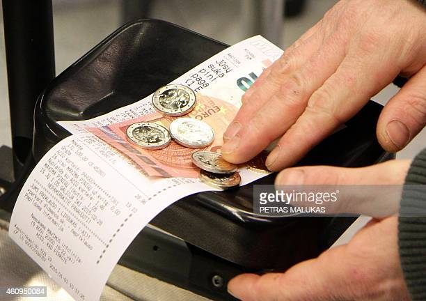 A customer pays in euro banknotes in a supermarket in Vilnius on January 1 2015 Lithuania switched over to the euro on Thursday becoming the last...