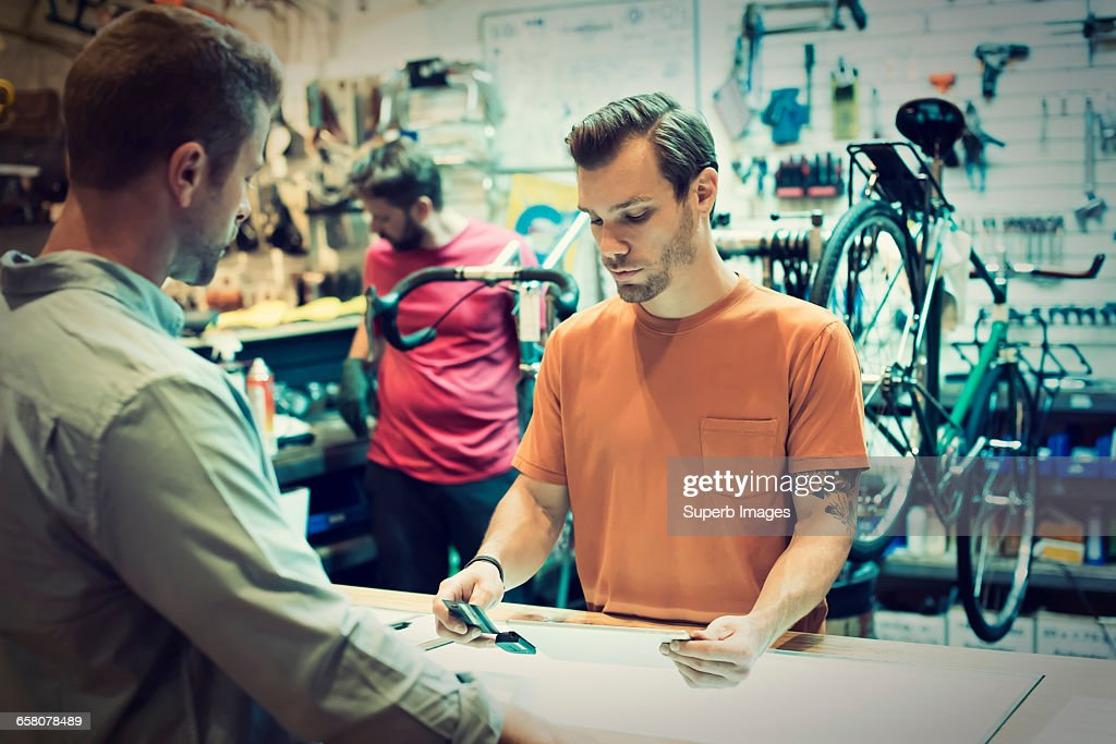 Customer pays with credit card in bike shop