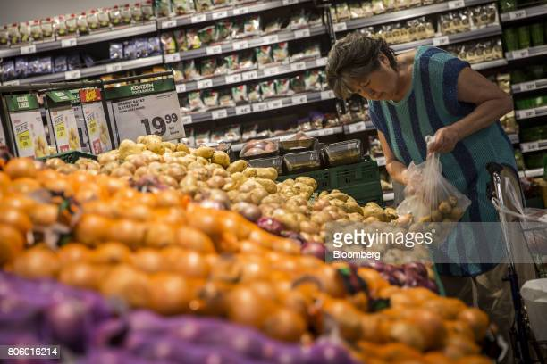 A customer picks potatoes from the fresh produce aisle inside a Super Konzum supermarket operated by Agrokor dd in Zagreb Croatia on Tuesday June 13...