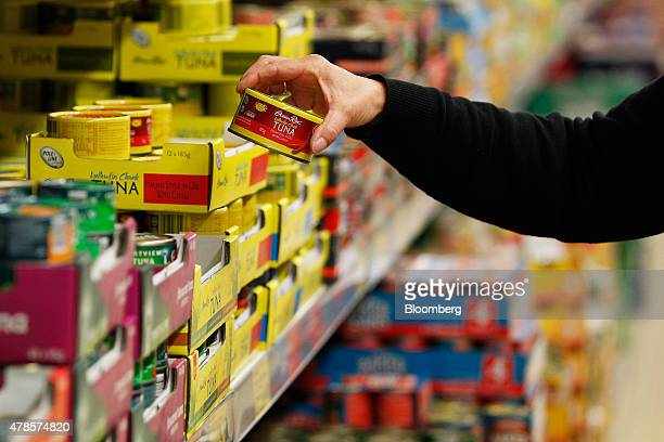 A customer picks up a can of Ocean Rise Yellowfin Chunk tuna at an Aldi Stores Ltd food store in Sydney Australia on Thursday June 25 2015...