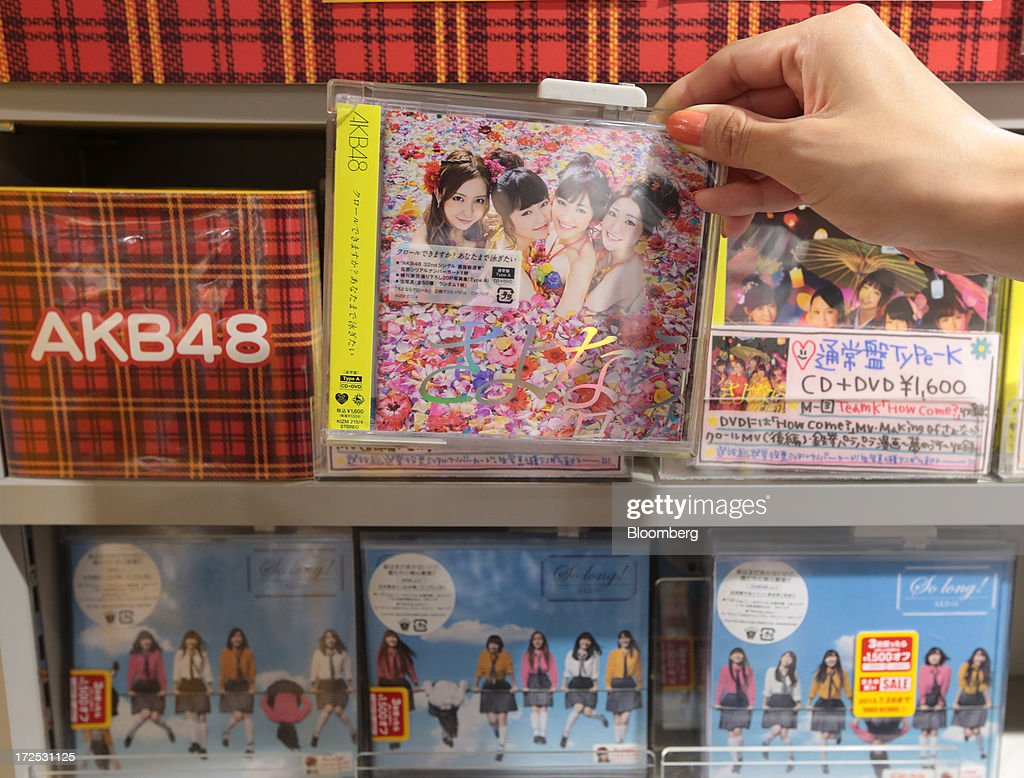 A customer picks up a music CD and DVD package by 'AKB48', a Japanese girl group, displayed on a shelf at a Tower Records Japan Inc. store in Tokyo, Japan, on Monday, July 1, 2013. Music sales in the country rose for the first time in five years, led by tunes delivered on CDs and other physical media, bucking the trend in developed markets as cheaper downloads gain ground. Physical media made up 82 percent of Japanese music sales last year, versus 37 percent in the U.S., said the Recording Industry Association of Japan. Photographer: Yuriko Nakao/Bloomberg via Getty Images