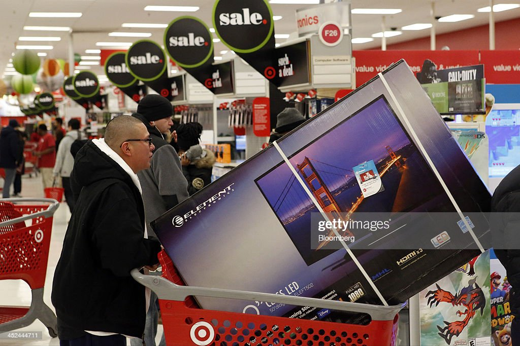 A customer picks up a shopping cart containing an Element Electronics 50-inch light-emitting diode (LED) high definition television at a Target Corp. store opening ahead of Black Friday in Chicago, Illinois, U.S., on Thursday, Nov. 28, 2013. U.S. retailers will kick off holiday shopping earlier than ever this year as stores prepare to sell some discounted items at a loss in a battle for consumers. Photographer: Patrick T. Fallon/Bloomberg via Getty Images