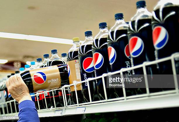 A customer picks up a two liter bottle of PepsiCo Inc soda from a supermarket shelf in Princeton Illinois US on Friday Oct 12 2012 PepsiCo Inc is...