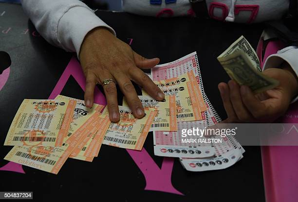 A customer picks up her California Powerball lottery tickets at the famous Bluebird Liquor store which is considered to be a lucky retailer of...
