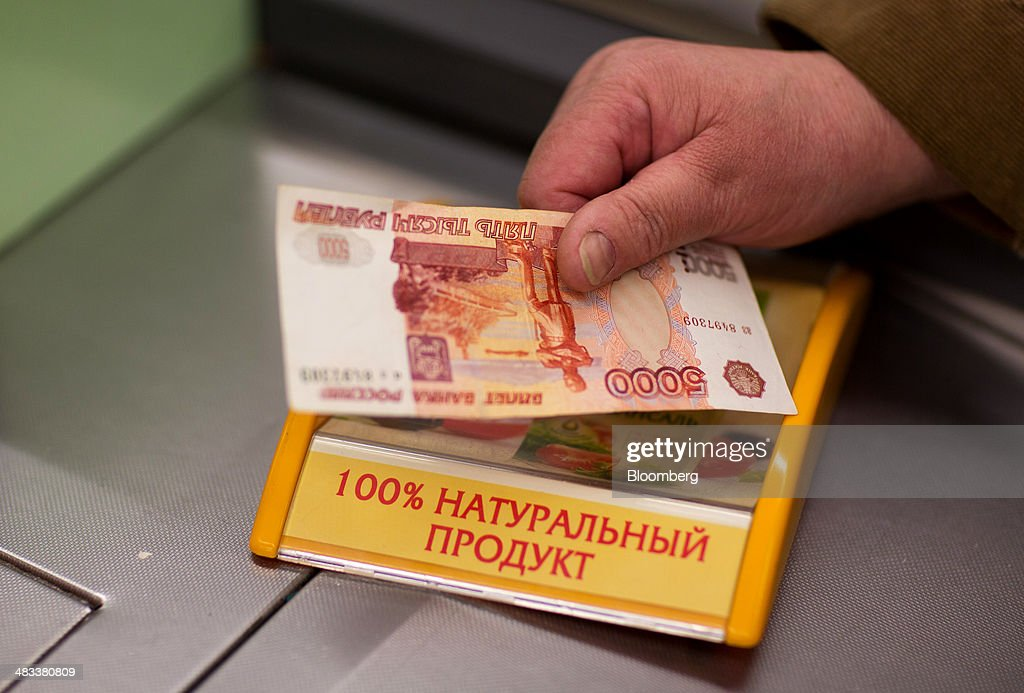 A customer places a 5000 ruble banknote on the counter to pay for goods at the check out desk inside a Dixy supermarket operated by OAO Dixy Group in Moscow, Russia, on Tuesday, April 8, 2014. Suppliers suffering from ruble depreciation this quarter are urging retailers to increase prices. Photographer: Andrey Rudakov/Bloomberg via Getty Images