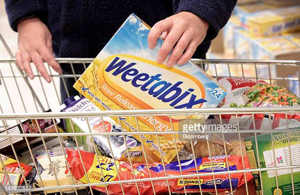 A customer places a packet of Weetabix breakfast cereal produced by Weetabix Ltd into a shopping cart in this arranged photograph at a supermarket in...