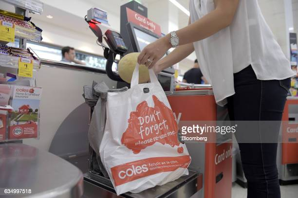 A customer places grocery items into a plastic bag at a self checkout counter in a Coles supermarket operated by Wesfarmers Ltd in the Richmond area...