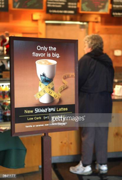 A customer places her coffee order beyond signage for new 'Skinny'Bou Lattes' at a Caribou Coffee store January 2 2004 in Mount Prospect Illinois...