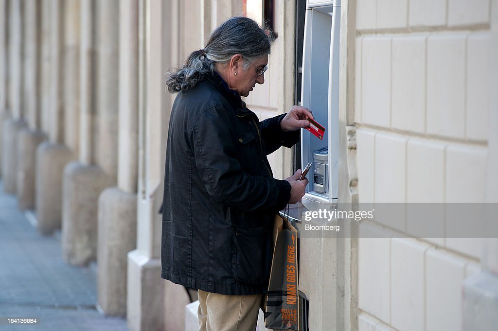 A customer places his card in an automated teller machine (ATM) operated by Banco Santander SA in Barcelona, Spain, on Wednesday, March 20, 2013. Officials from the troika of international creditors -- the ECB, the International Monetary Fund and the European Commission -- are in Cyprus discussing further capital controls and possibly extending a bank holiday to the end of the week, a European official familiar with the talks said on condition of anonymity because the discussions are confidential. Photographer: David Ramos/Bloomberg via Getty Images