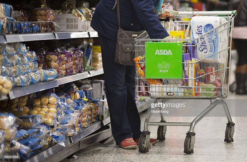 A customer places items from a display of bread goods into her shopping cart inside an Asda supermarket, the U.K. retail arm of Wal-Mart Stores Inc., in Watford, U.K., on Thursday, Oct. 17, 2013. U.K. retail sales rose more than economists forecast in September as an increase in furniture demand led a rebound from a slump the previous month. Photographer: Simon Dawson/Bloomberg via Getty Images