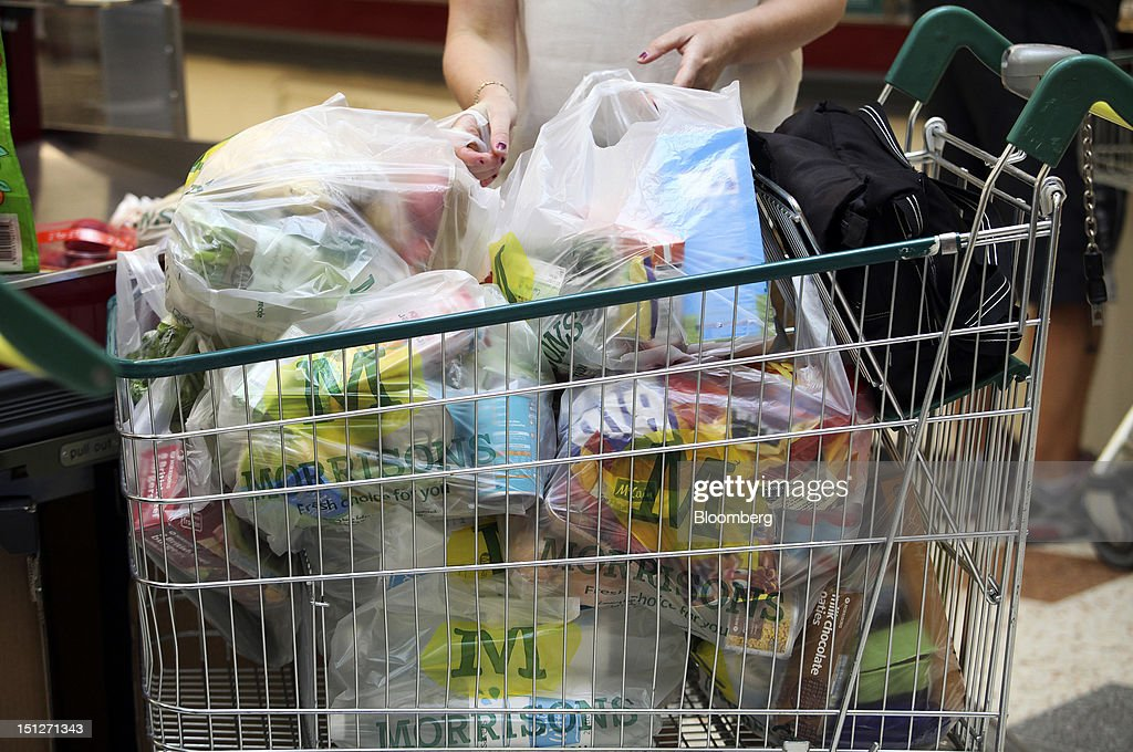 A customer places Morrisons-branded bags into a shopping cart at the checkout of a William Morrison Supermarkets Plc grocery store in Erith, U.K., on Wednesday, Sept. 5, 2012. Morrisons announced that 60 percent of store openings will be in southern England next year as it shifts attention from its northern heritage. Photographer: Chris Ratcliffe/Bloomberg via Getty Images