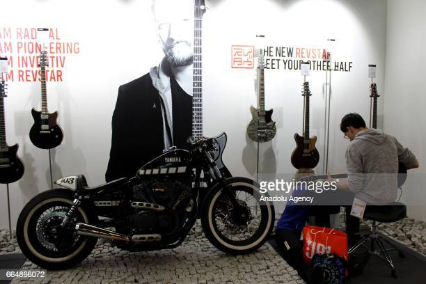 A customer plays a guitar presented at the International Trade Fair for musical instruments sheet music music production and marketing 'Musikmesse'...
