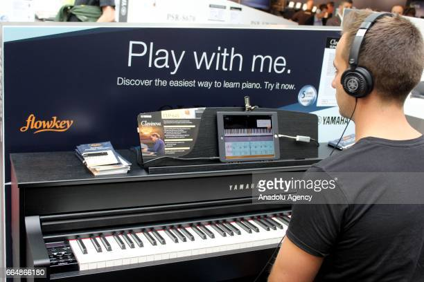 A customer plays a keyboard piano presented at the International Trade Fair for musical instruments sheet music music production and marketing...