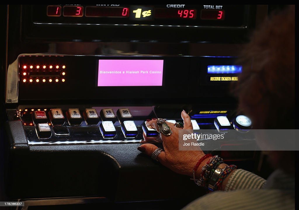 A customer plays a slot machine in the casino that will hold its grand opening on Friday located in the Hialeah Park Race Track which first opened in 1925 on August 28, 2013 in Hialeah, Florida. The new casino is located in the same complex as the race track which in its heyday was known as the 'the worlds most beautiful race course.'
