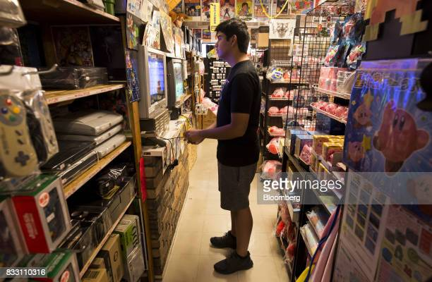 A customer plays a video game on the Nintendo Co Super Nintendo Entertainment System console at the Super Potato video game store in the Akihabara...