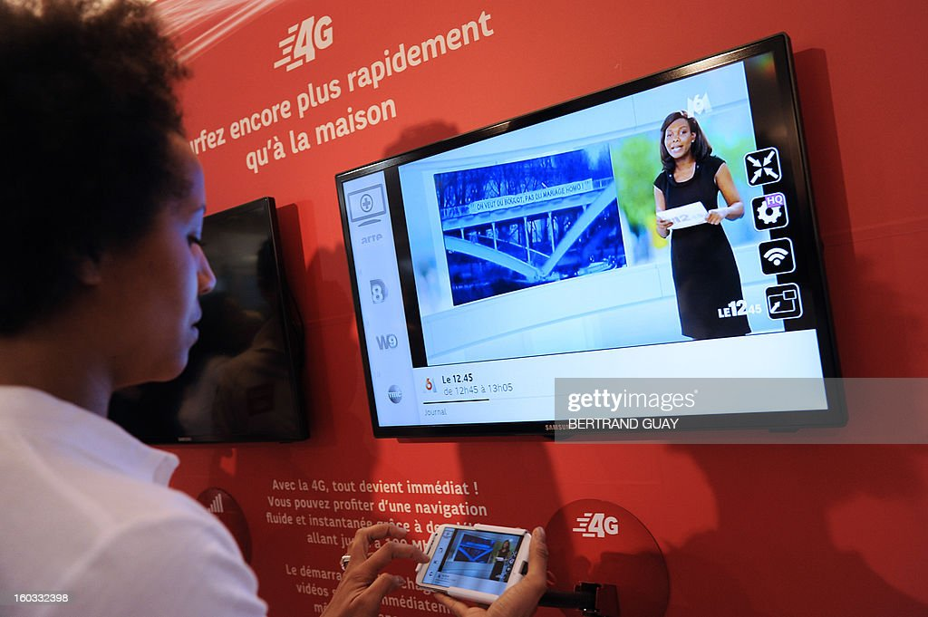 A customer plays a video on a mobile phone during the launch of the SFR 4G monile network on January 29, 2013 in La Defense, Paris business district. AFP PHOTO/ BERTRAND GUAY