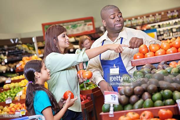 Cliente a apontar para os tomates com Supermercado produzir manager