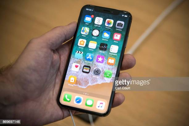 A customer poses with an iPhone X as he purchases one upon its release in the UK on November 3 2017 in London England The iPhone X is positioned as a...